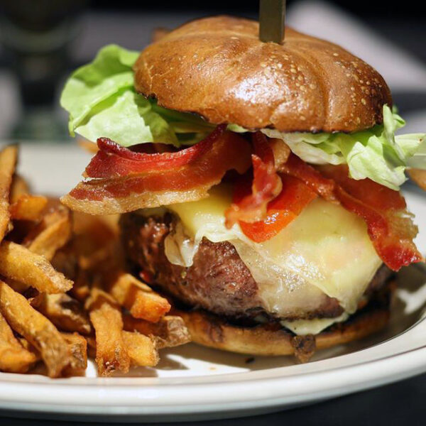Burger with bacon, cheese and lettuce on plate with fries